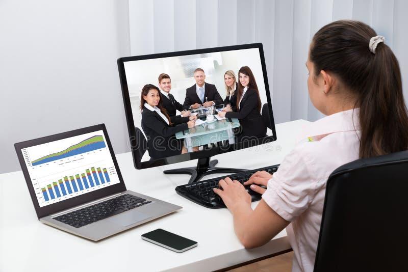 Mulher de negócios Videoconferencing On Computers imagem de stock