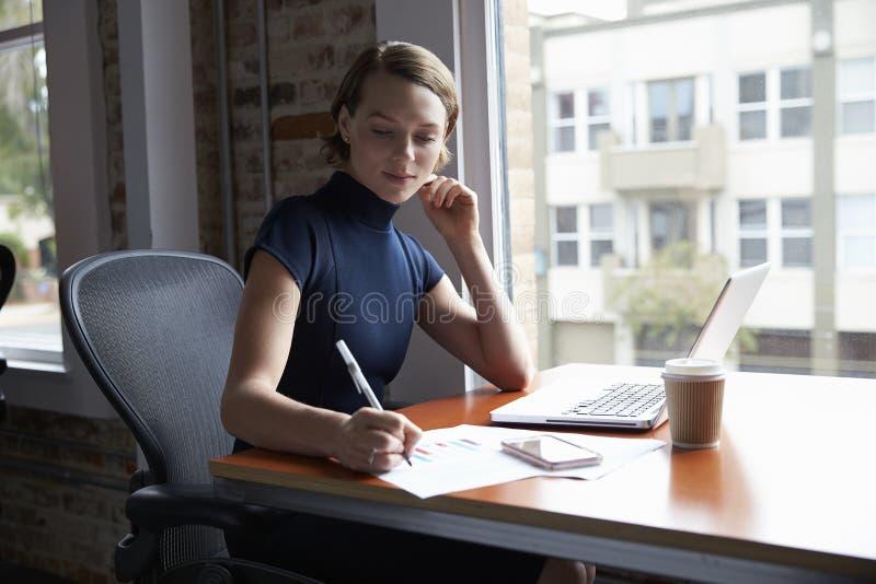 Mulher de negócios Working On Laptop e notas da fatura no original fotos de stock royalty free