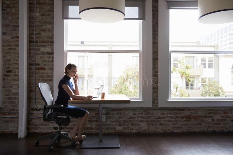 Mulher de negócios Working On Laptop e telefonema da fatura fotos de stock