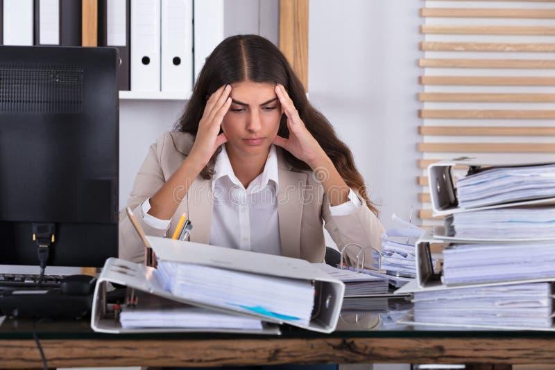 Mulher de negócios Working At Office com a pilha de dobradores na mesa fotografia de stock