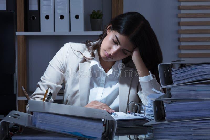 Mulher de negócios Working At Office com a pilha de dobradores na mesa fotos de stock royalty free