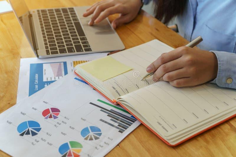 Mulher de neg?cio nova que senta-se na tabela e que toma notas no caderno Documentos do investimento do empr?stimo fotografia de stock