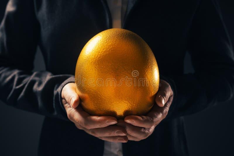 Mulher de neg?cios bem sucedida que guarda o ovo dourado fotos de stock