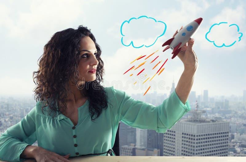 A mulher de neg?cios lan?a sua empresa com um foguete Conceito da partida e da inova??o imagens de stock royalty free