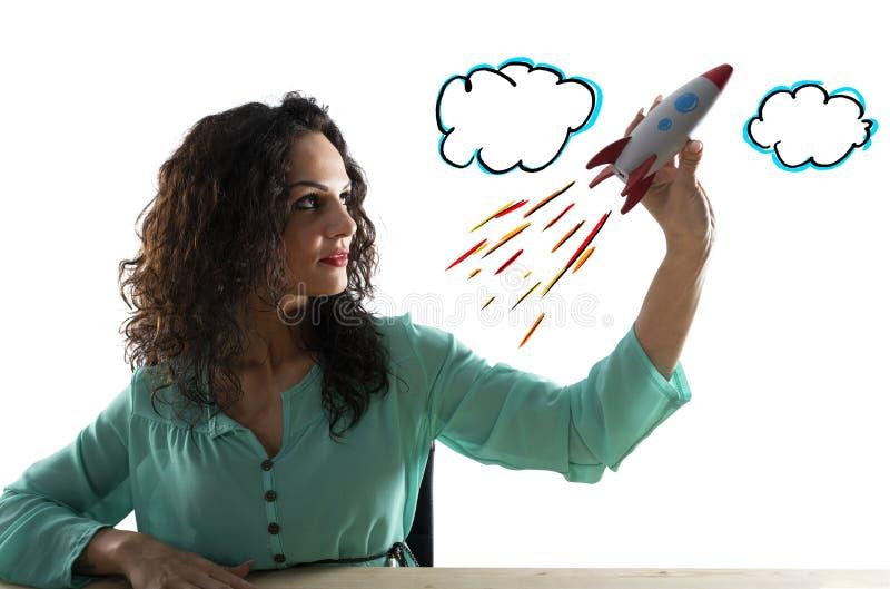 A mulher de neg?cios lan?a sua empresa com um foguete Conceito da partida e da inova??o imagem de stock