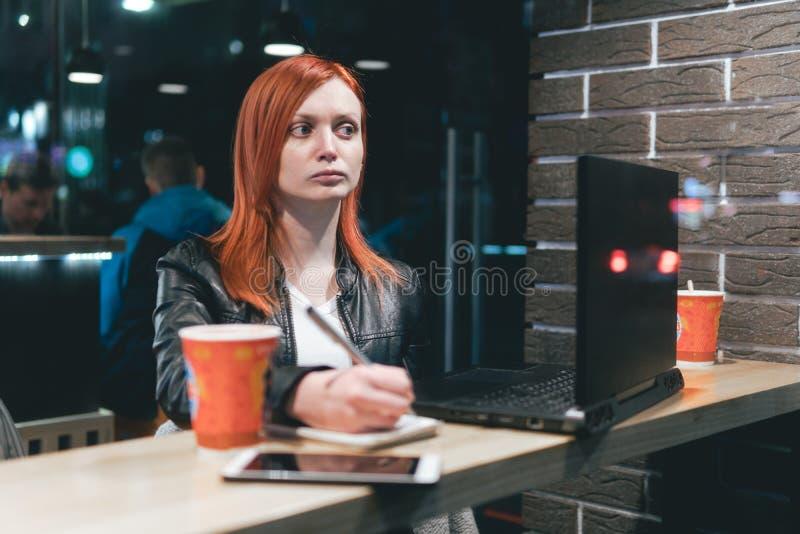 Mulher de neg?cios, menina que guarda uma pena, escrevendo em um caderno, port?til no caf?, smartphone, pena, computador do uso O imagem de stock royalty free