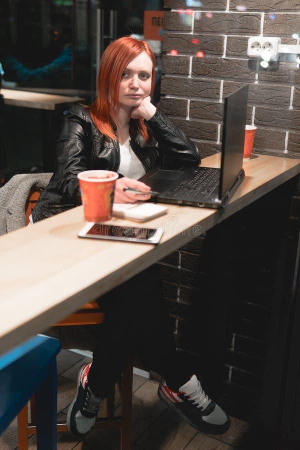 Mulher de neg?cios, menina que trabalha no port?til no caf?, smartphone, pena, computador do uso O Freelancer trabalha remotament foto de stock royalty free