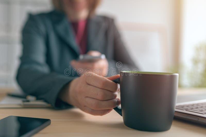 Mulher de neg?cios que texting no telefone celular durante a ruptura de caf? do escrit?rio imagem de stock