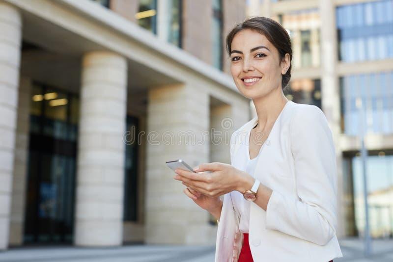 Mulher de neg?cios de sorriso que guardara o smartphone fotos de stock royalty free