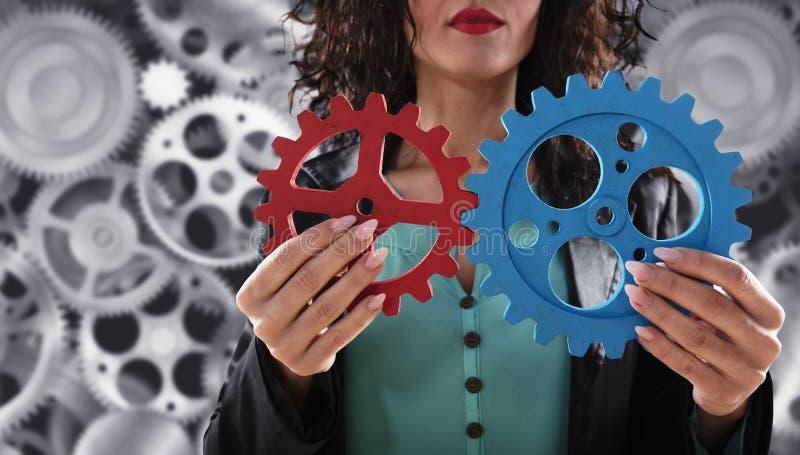 A mulher de neg?cios tenta conectar partes das engrenagens Conceito dos trabalhos de equipe, da parceria e da integra??o foto de stock