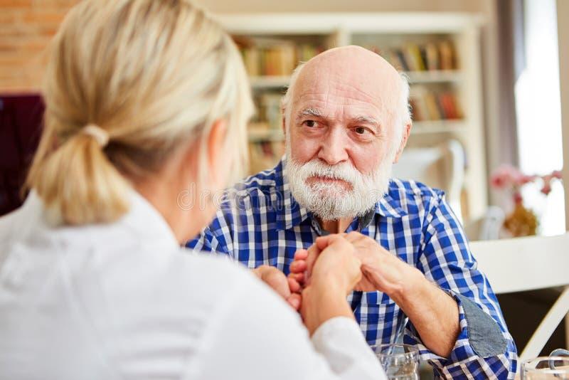 A mulher de nutrição consola o sênior demente imagens de stock