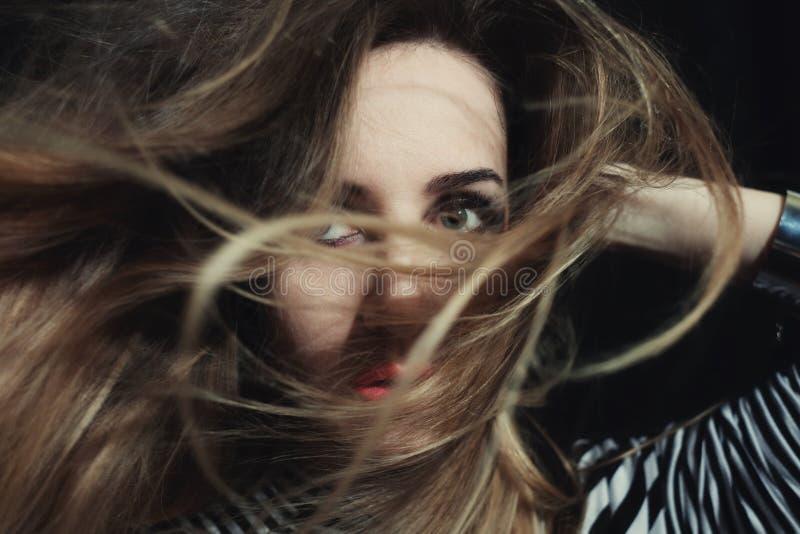 Mulher de olhos azuis com seu cabelo louro envolvido em torno de sua cara foto de stock