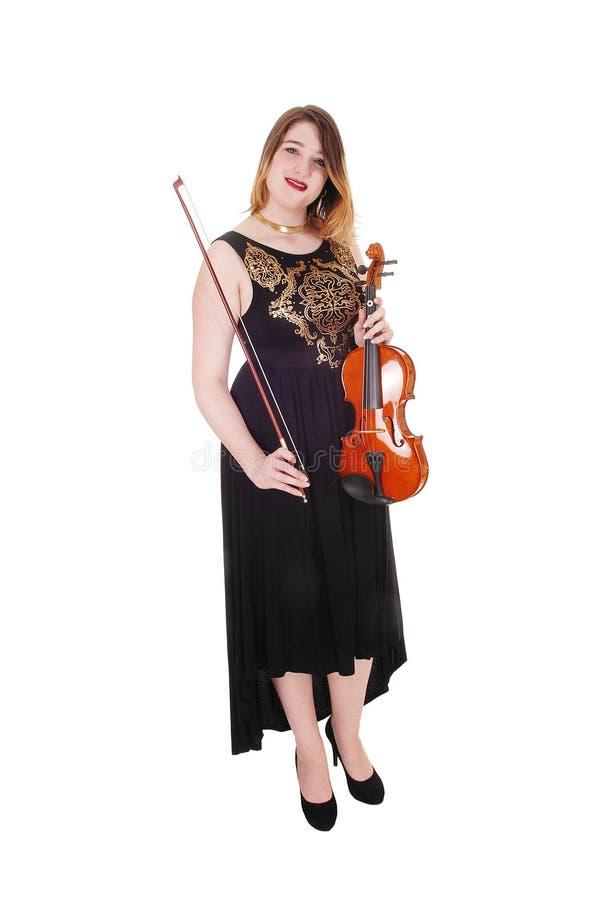 Mulher de pé com um vestido longo segurando seu violino foto de stock