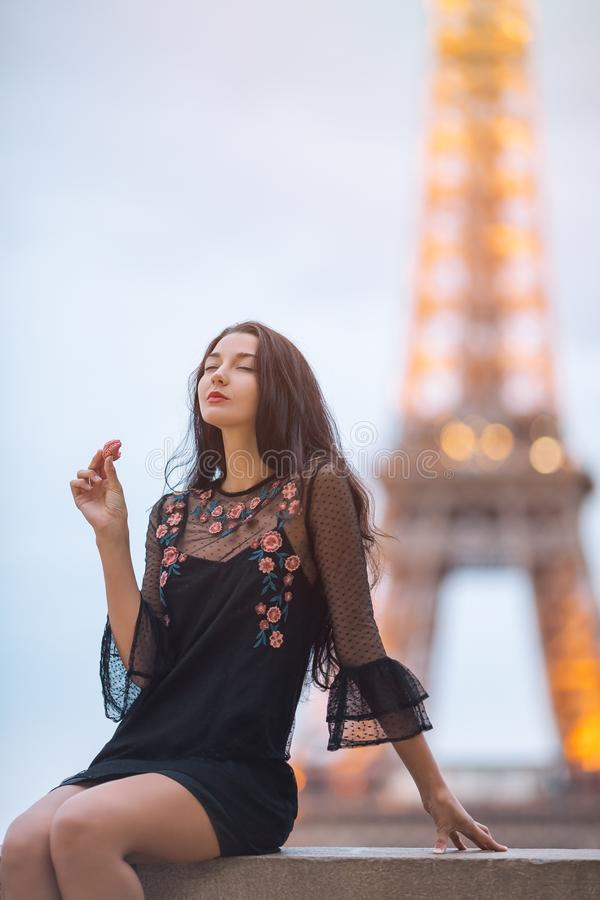 Mulher de Paris que sorri comendo o macaron da pastelaria francesa em Paris contra a torre Eiffel foto de stock