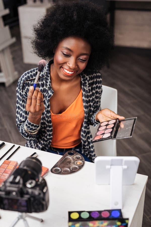 Mulher de pele escura bonita com o batom coral que guarda a paleta do ruge fotografia de stock