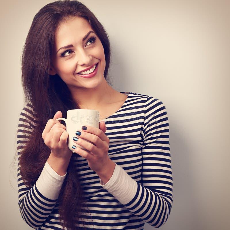 Mulher de pensamento calma bonita que bebe o café quente do copo Vint fotografia de stock