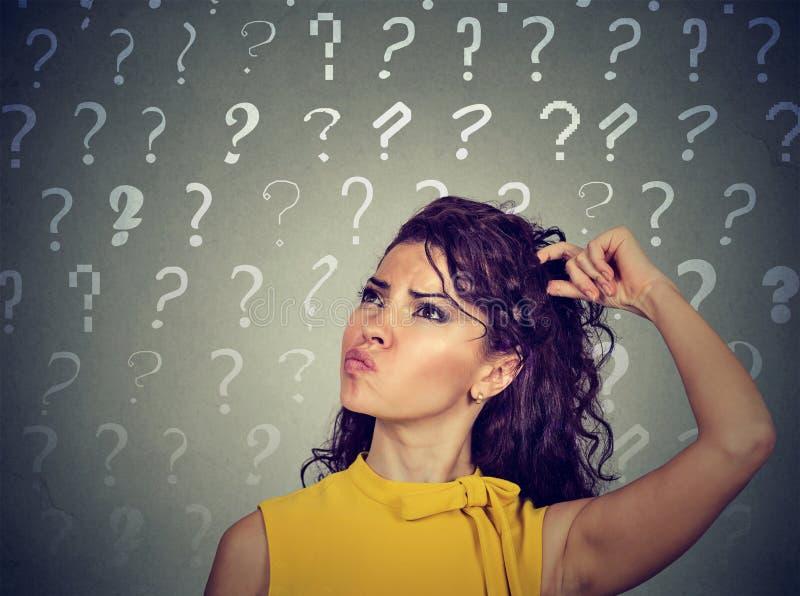 A mulher de pensamento confusa que risca a cabeça tem muitas perguntas fotografia de stock royalty free