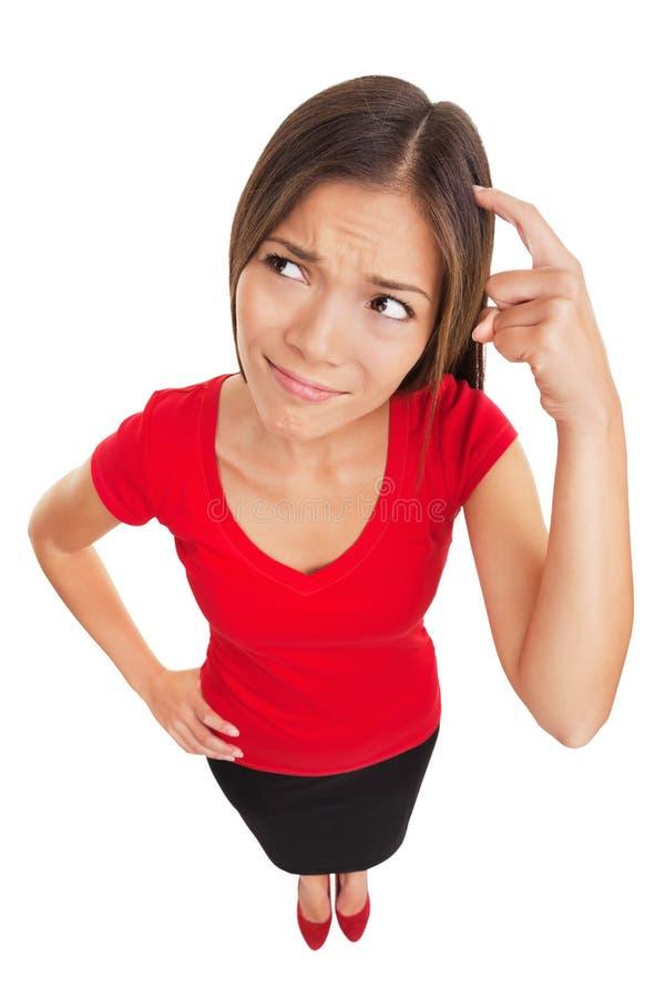 Mulher confusa que risca sua cabeça imagens de stock