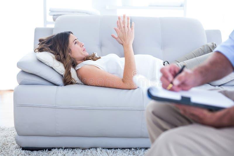Mulher de Preganant que relaxa no sofá com terapeuta foto de stock