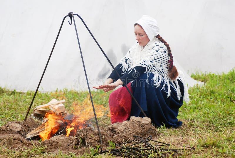 Mulher de Reenactor que aquece suas mãos pelo fogo fotografia de stock royalty free