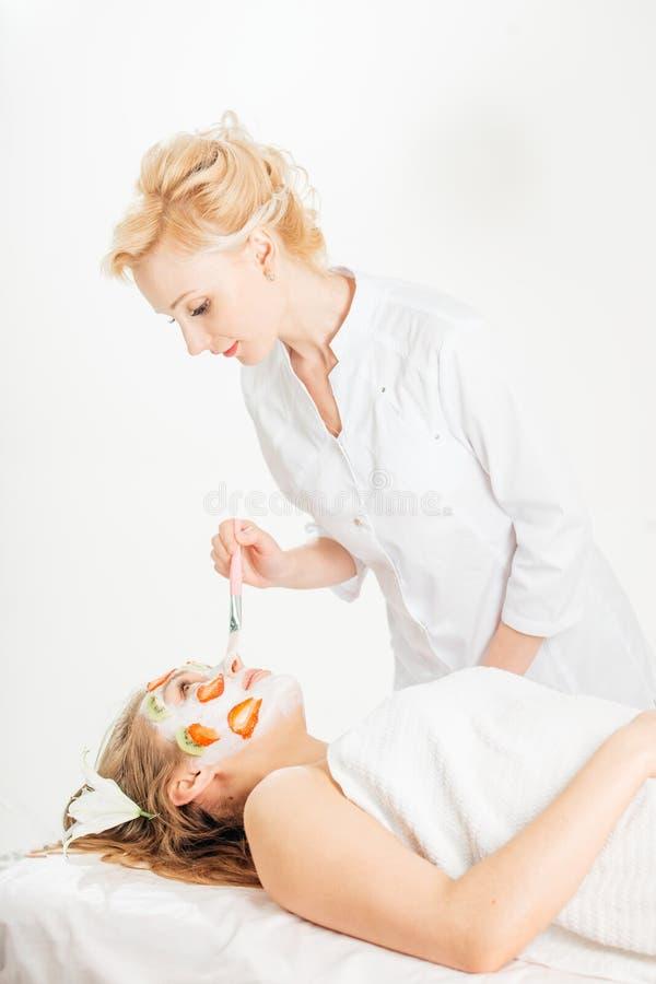 Mulher de relaxamento bonita nova que tem a máscara de umedecimento aplicada imagem de stock royalty free
