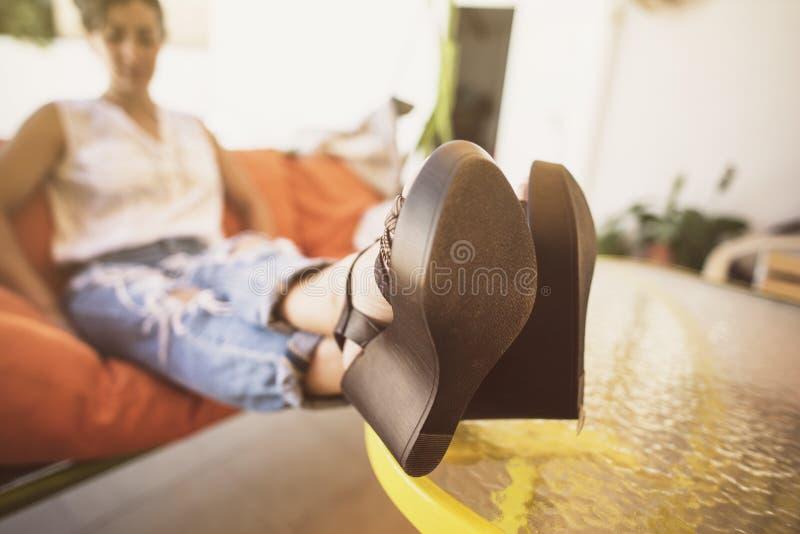 Mulher de relaxamento na imagem do ar livre com os saltos na tabela imagens de stock
