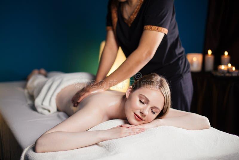 Mulher de relaxamento nos termas da beleza do bem-estar que têm a massagem da terapia do aroma fotografia de stock