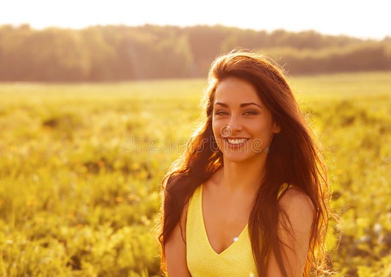 Mulher de relaxamento de sorriso natural toothy bonita que olha feliz com cabelo surpreendente longo no fundo brilhante do verão  fotografia de stock