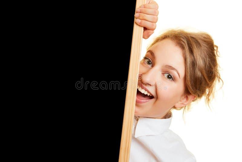 Mulher de riso atrás do quadro preto foto de stock
