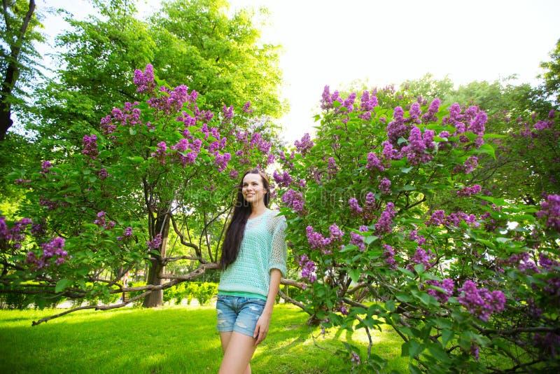 Mulher de riso com cabelo saudável longo no parque em um fundo lilás fotos de stock royalty free