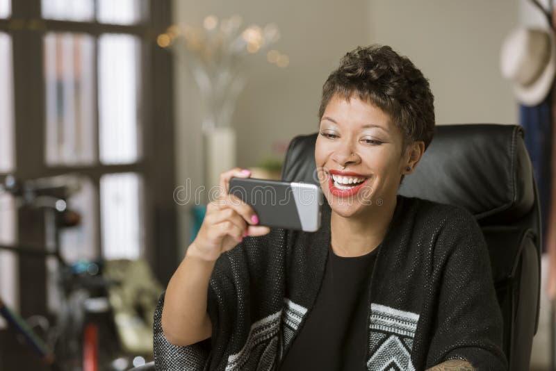 Mulher de riso com um telefone em seu escritório fotografia de stock royalty free