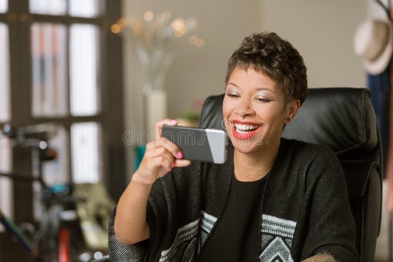 Mulher de riso com um telefone em seu escrit?rio fotografia de stock royalty free