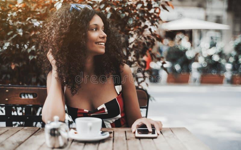 Mulher de riso encaracolado em um café da rua com o telefone celular imagem de stock royalty free