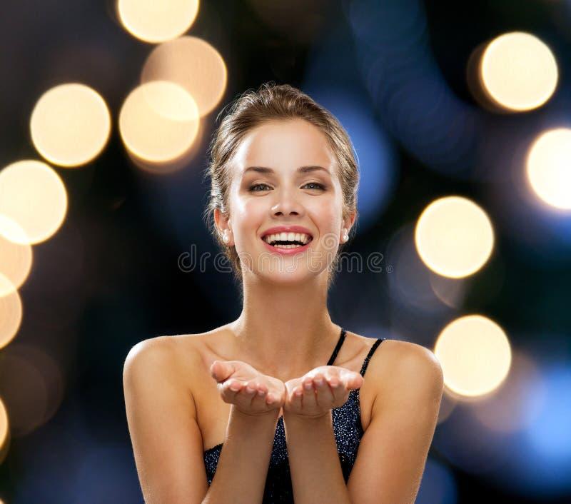 Mulher de riso no vestido de noite que guarda algo fotos de stock