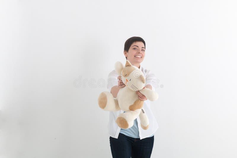 Mulher de riso nova com cabelo curto no estilo ocasional que dá o gato dianteiro do brinquedo do luxuoso e que olha a câmera com  fotografia de stock royalty free