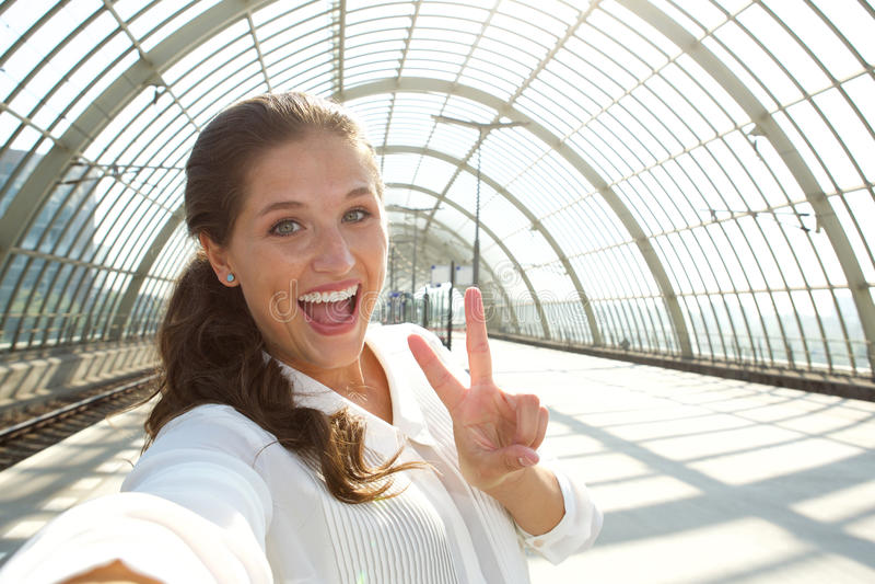 Mulher de riso nova que toma o selfie com sinal de paz fotografia de stock