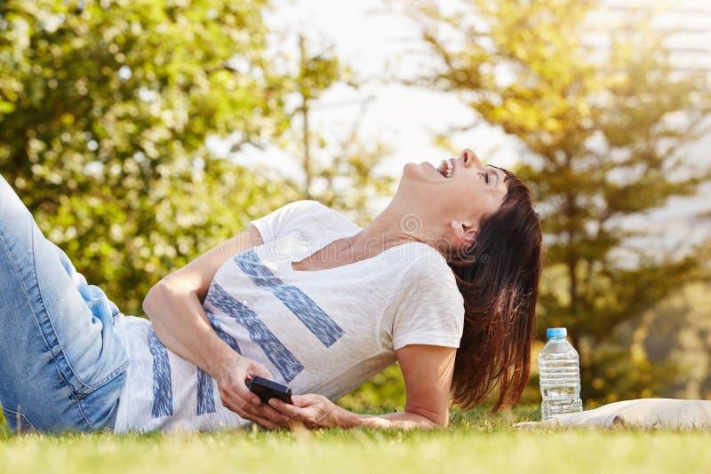 Mulher de riso que encontra-se na grama fora com telefone celular fotografia de stock royalty free