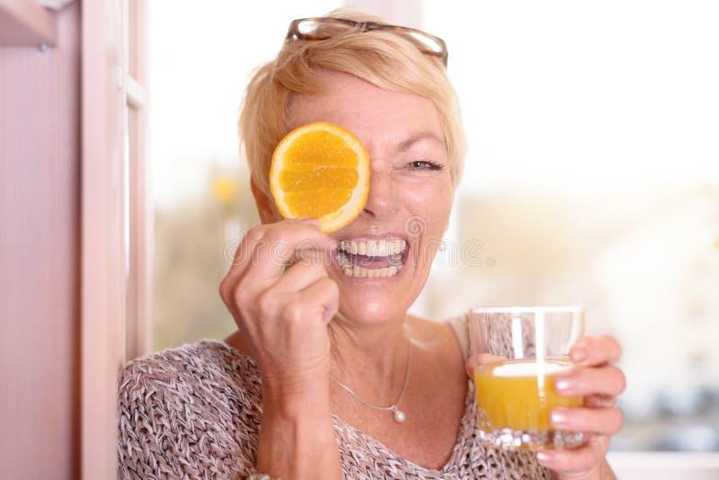 Mulher de riso que guarda uma laranja a seu olho foto de stock royalty free