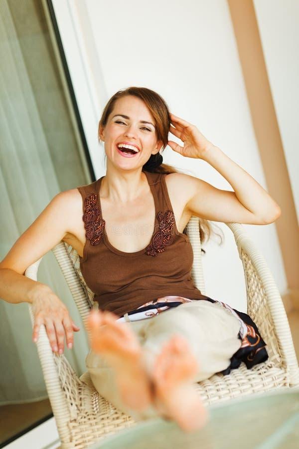 Mulher de riso que relaxa no terraço imagens de stock royalty free