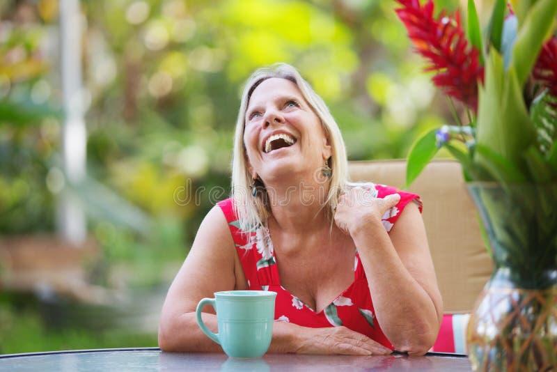 Mulher de riso que senta-se na tabela imagens de stock
