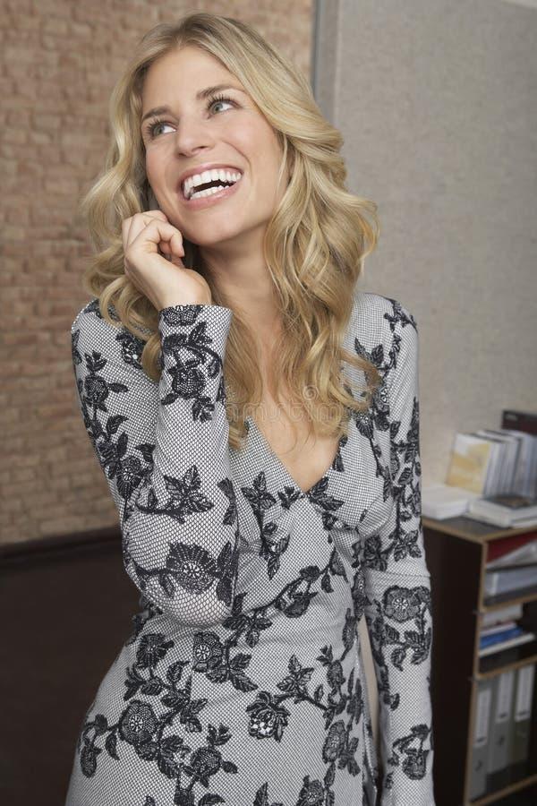 Mulher de riso que usa o telefone celular no escritório foto de stock