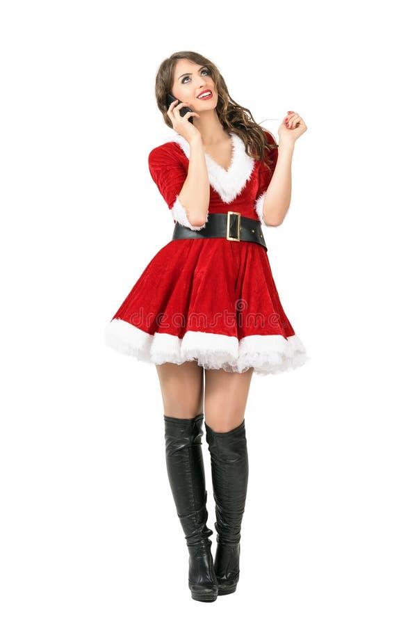 Mulher de Santa Claus do Natal feliz que fala no telefone celular que olha acima fotografia de stock royalty free