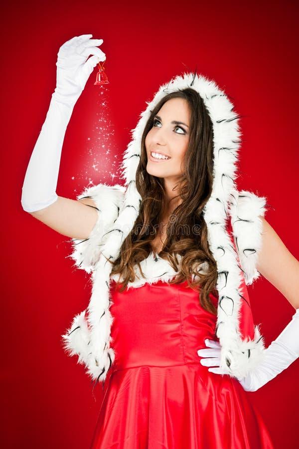 Mulher de Santa que prende o sino mágico do xmas fotografia de stock