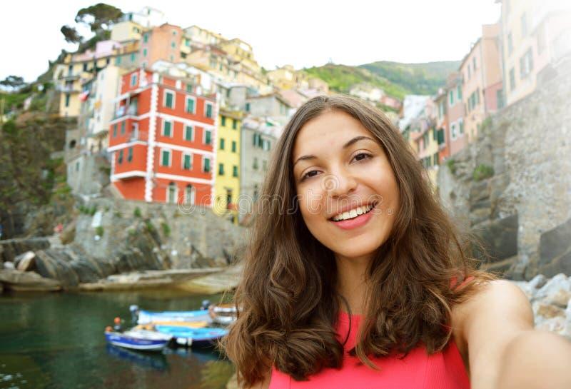 Mulher de Selfie que toma o autorretrato com a vila italiana típica no fundo Menina que guarda a câmera do smartphone para tomar  foto de stock royalty free