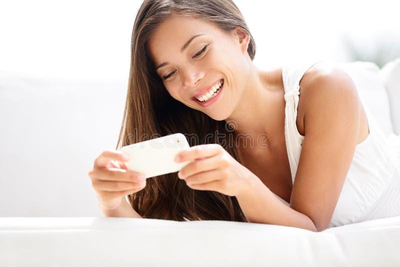 Mulher de Smartphone que usa o sorriso do app feliz imagens de stock