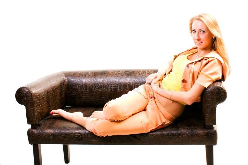 Mulher de Smilling que senta-se no sofá imagem de stock