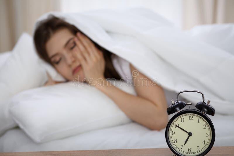Mulher de sono bonita que encontra-se na cama e que tenta acordar com despertador Menina que tem o problema com levantar-se cedo foto de stock royalty free