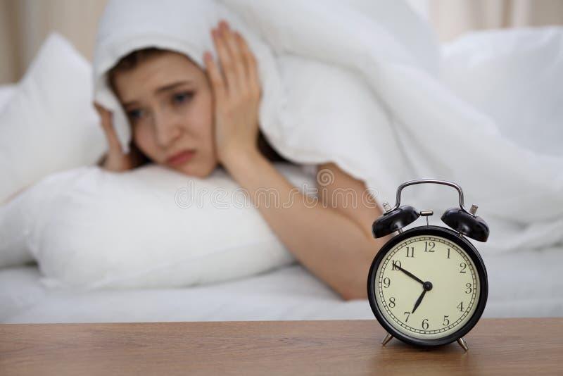 Mulher de sono bonita que encontra-se na cama e que tenta acordar com despertador Menina que tem o problema com levantar-se cedo imagens de stock royalty free