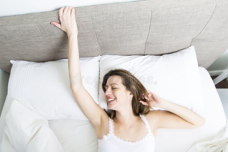 Mulher de sono nova no quarto em casa que veste no branco fotografia de stock