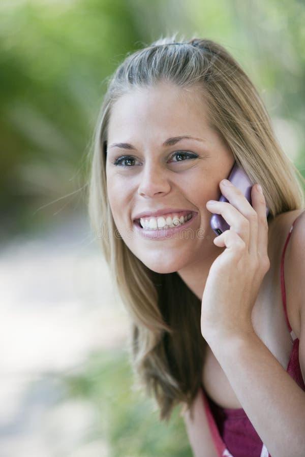 Mulher de sorriso ao ar livre com telefone de pilha fotografia de stock